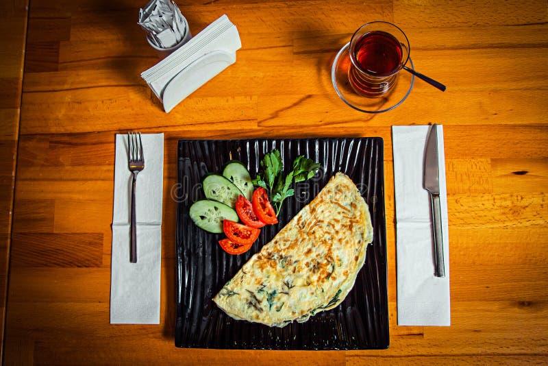 在一块黑时髦的板材和一杯的全国盘在一张木桌上的黑土耳其茶 免版税库存照片