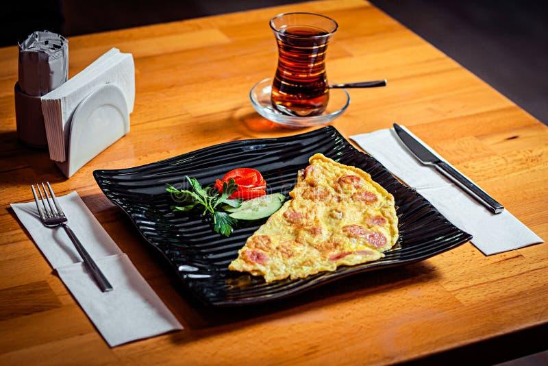 在一块黑时髦的板材和一杯的全国盘在一张木桌上的黑土耳其茶 库存照片