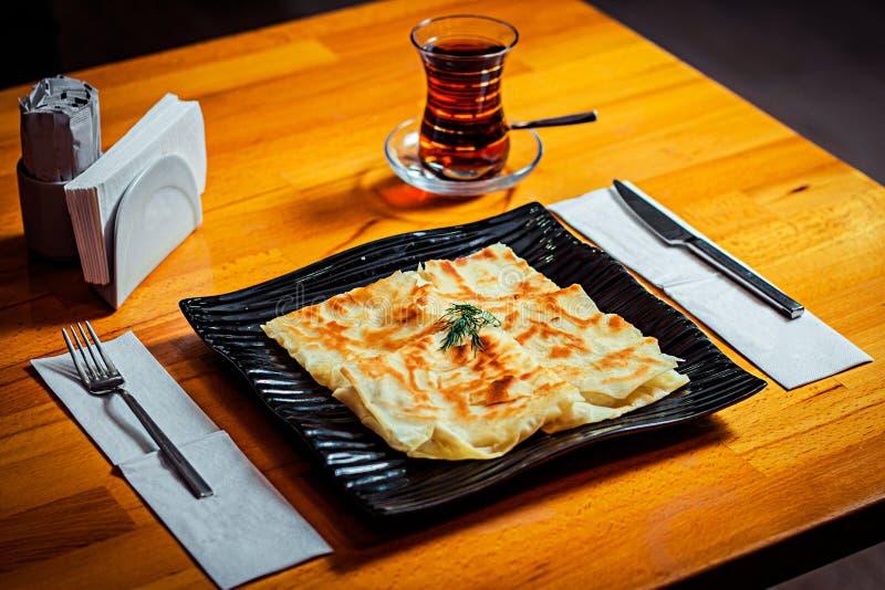 在一块黑时髦的板材和一杯的全国盘在一张木桌上的黑土耳其茶 库存图片