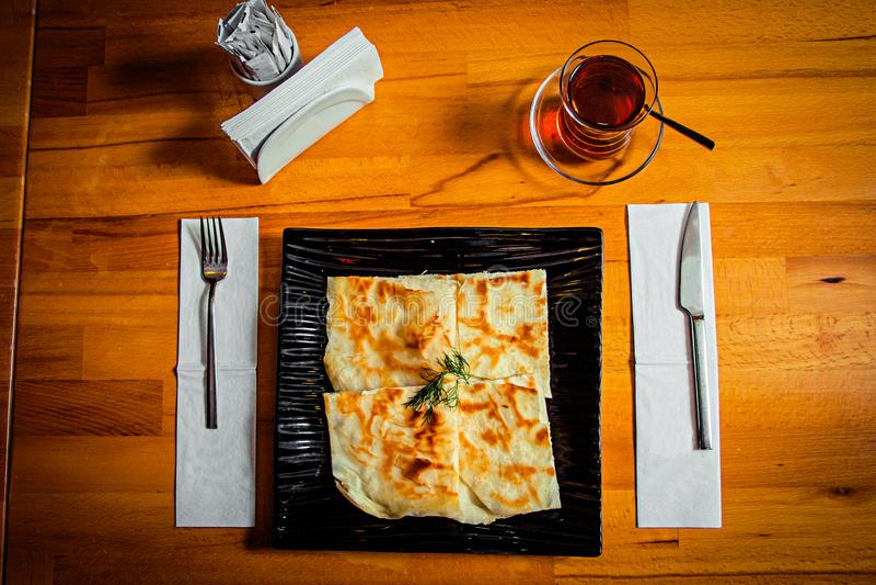 在一块黑时髦的板材和一杯的全国盘在一张木桌上的黑土耳其茶 免版税库存图片
