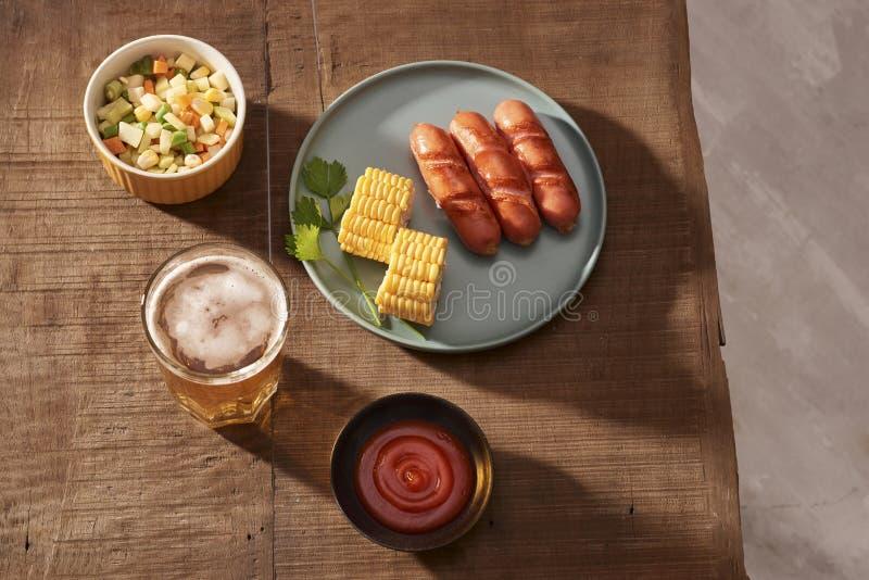 在一块黑暗的板材、肉盘在黑暗的木背景,热的香肠用香料和盐的家庭烤香肠在家 免版税库存照片