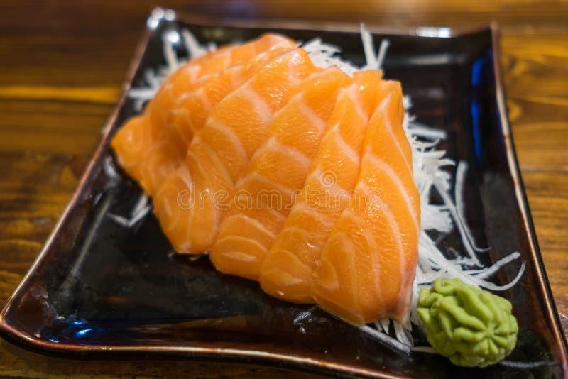 在一块黑陶瓷板材的三文鱼生鱼片有山葵的部分的 免版税库存照片