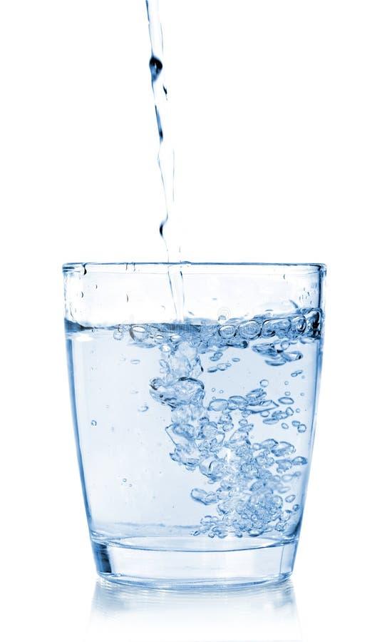 在一块玻璃的倾吐的水在白色 免版税库存图片