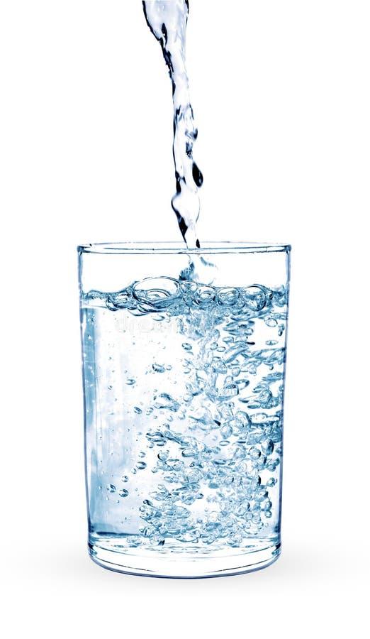 在一块玻璃的倾吐的水在白色 免版税图库摄影