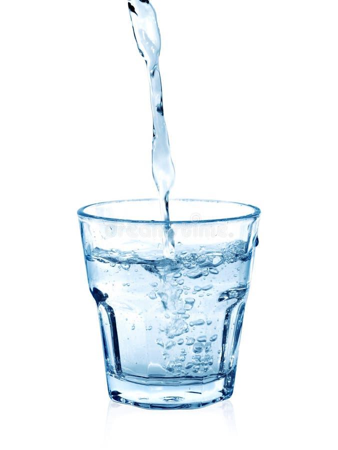 在一块玻璃的倾吐的水在白色 免版税库存照片