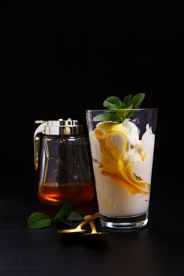 在一块玻璃的冰淇凌用蜂蜜 库存照片