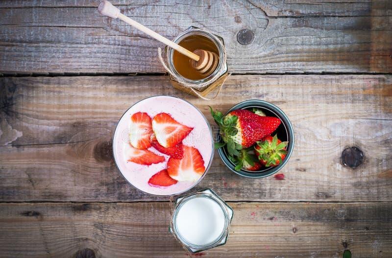 在一块玻璃的草莓圆滑的人用在旁边蜂蜜和酸奶 免版税库存照片