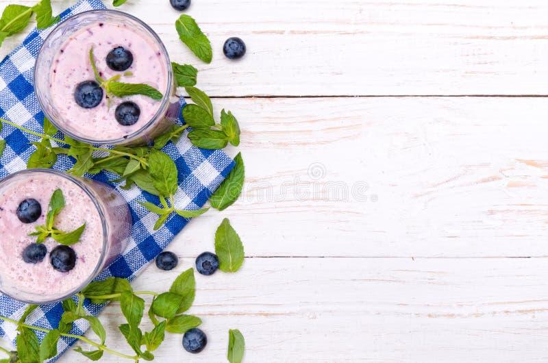在一块玻璃的蓝莓圆滑的人在一张白色木桌上 免版税库存图片