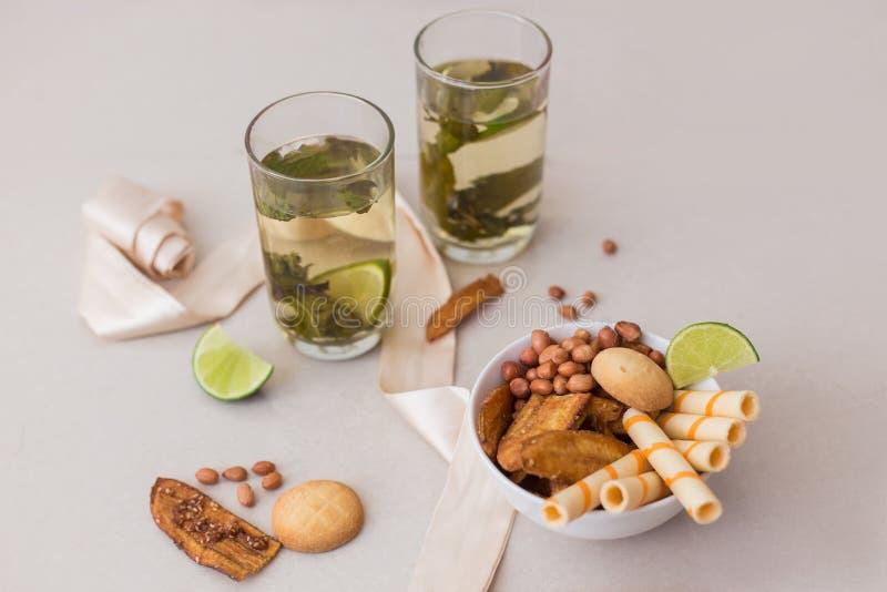 在一块玻璃的绿茶与石灰和曲奇饼 免版税库存照片