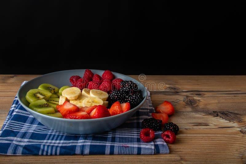 在一块greyblue板材的健康水果沙拉在木古色古香的桌和减速火箭的蓝色桌布上 免版税库存照片