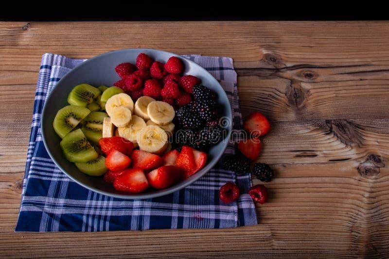 在一块greyblue板材的健康水果沙拉在木古色古香的桌和减速火箭的蓝色桌布上 库存照片