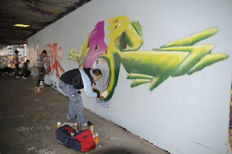 在一堵无装饰的墙上的街道艺术家繁忙的绘画街道画 免版税库存照片