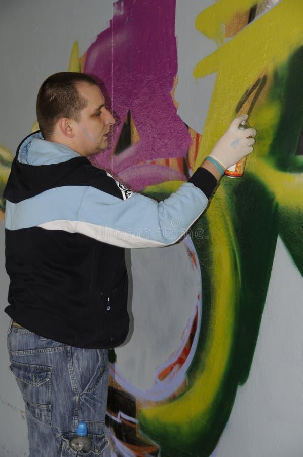 在一堵无装饰的墙上的街道艺术家繁忙的绘画街道画 免版税库存图片