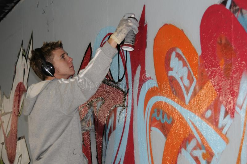 在一堵无装饰的墙上的街道艺术家繁忙的绘画街道画 库存照片