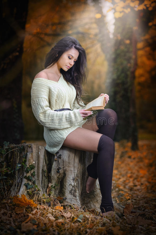 读在一处浪漫秋天风景的年轻白种人肉欲的妇女一本书。相当女孩画象在森林里在秋天 免版税库存图片