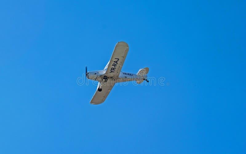 在一天空蔚蓝的小白色飞机飞行,在一个美好的夏日 免版税图库摄影