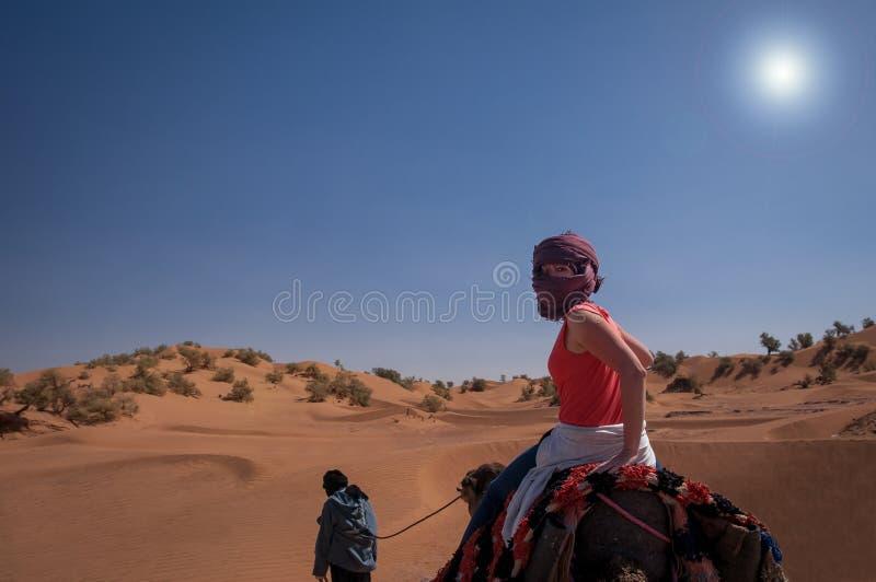 在一头独峰驼的年轻女人骑马在摩洛哥沙子沙漠 免版税库存照片