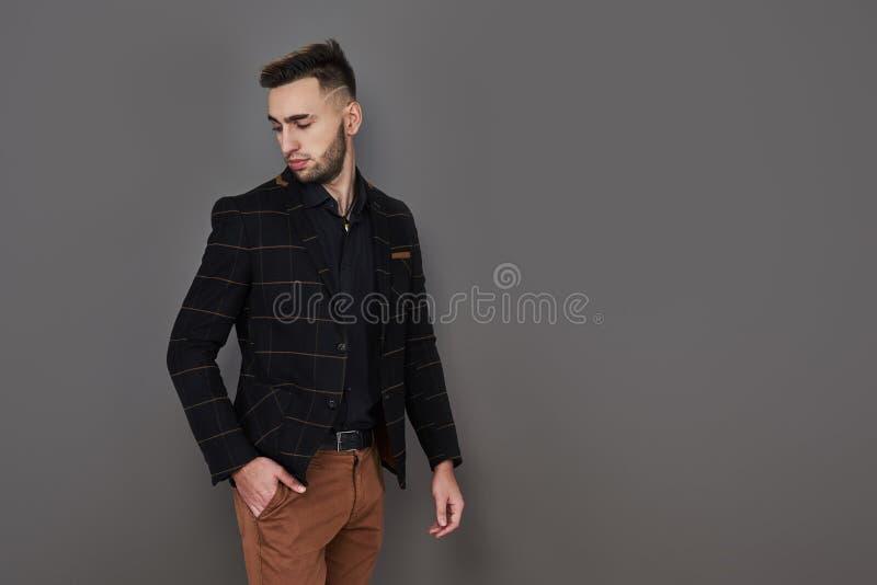 在一套棕色衣服的成功的年轻商人与摆在反对与拷贝的深灰背景的可爱的真正微笑 免版税库存照片