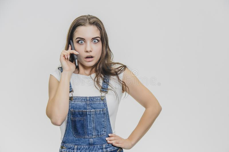 在一套蓝色牛仔布衣服和白色T恤打扮的一年轻美女 她与在腰部的一只手通电话 免版税库存图片