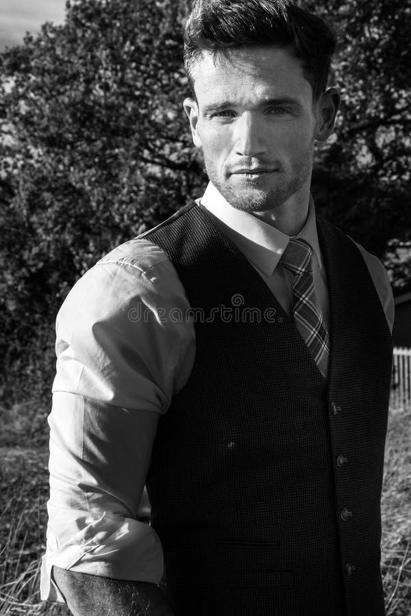 在一套衣服打扮的俊男在有树和领域的乡下后边在他后 免版税库存照片