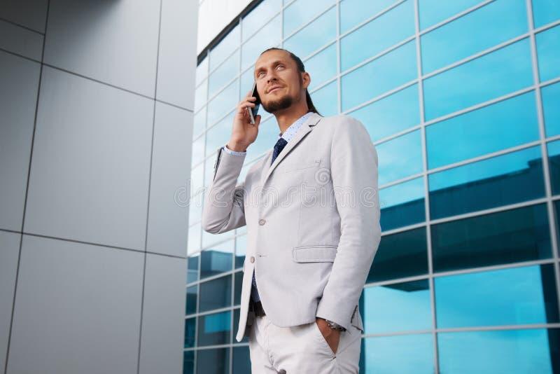 在一套轻的衣服的商人谈话在商业中心的背景的电话 免版税库存图片