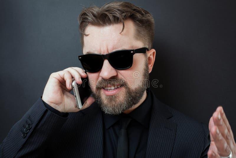 在一套黑衣服的一个商人由有他的下级的电话发誓 太阳镜的一个人在电话里说,打手势与他的h 库存照片