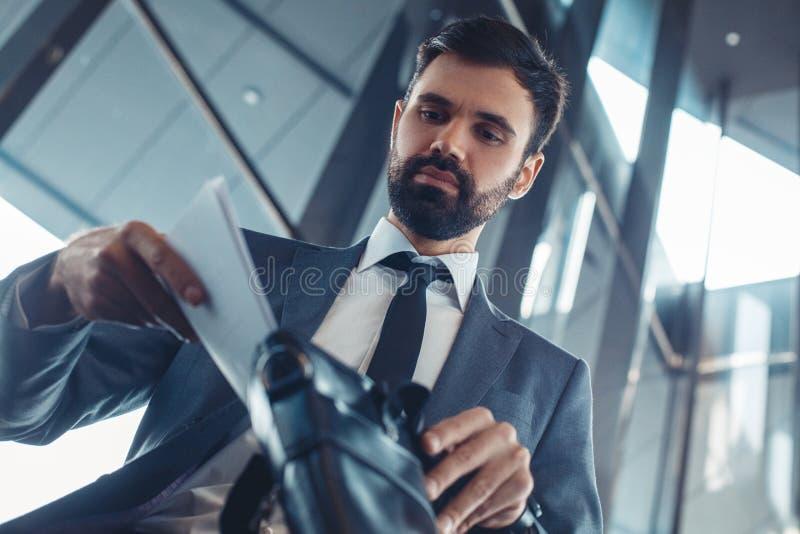 在一套fromal衣服的商人在投入文件的商业中心里面 库存图片