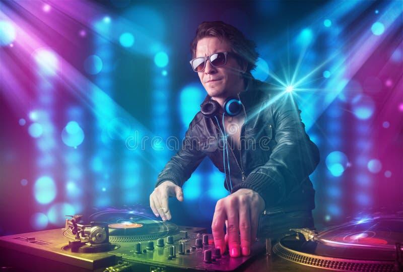 在一家俱乐部的Dj混合的音乐与蓝色和紫色光 免版税图库摄影