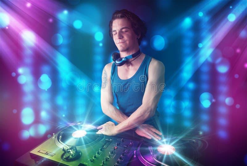 在一家俱乐部的Dj混合的音乐与蓝色和紫色光 皇族释放例证