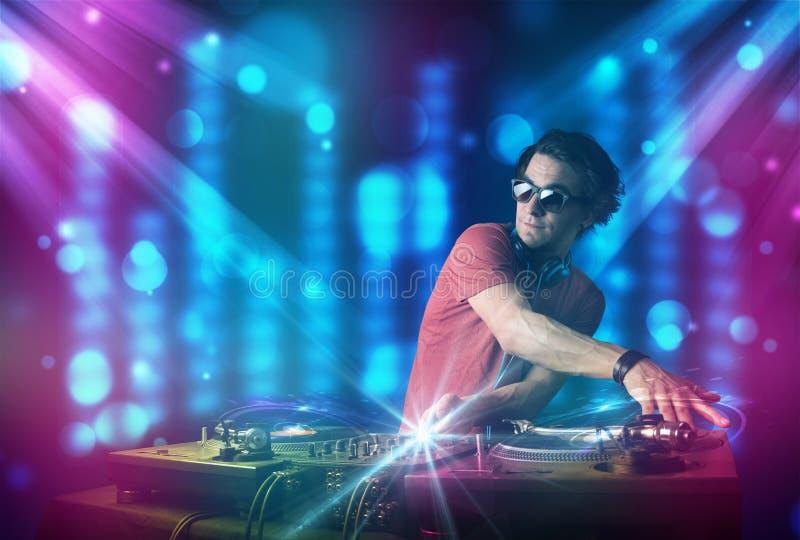 在一家俱乐部的Dj混合的音乐与蓝色和紫色光 库存照片