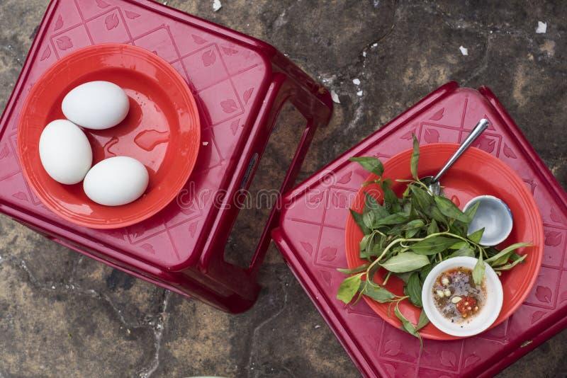 在一家街道餐馆低头胚胎鸡蛋、调味汁和草本在凳子在越南 库存照片
