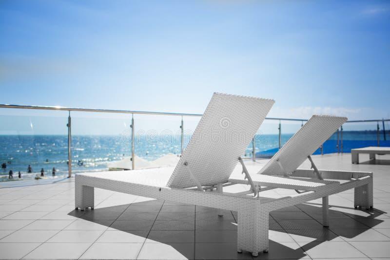 在一家高级旅馆的透明阳台的很多轻便折叠躺椅 与塑料白色轻便马车休息室的美好的海风景 库存图片