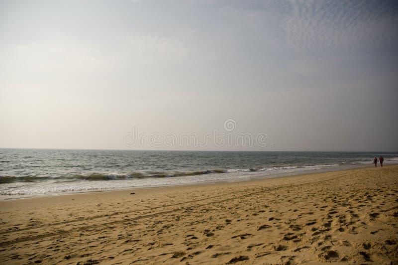 在一对年长夫妇在距离走在日落的海洋的一个离开的海滩 库存照片