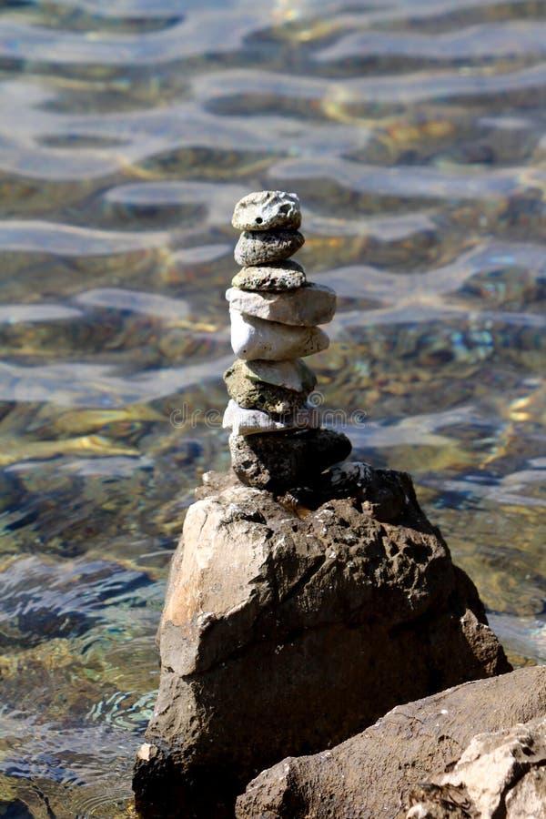 在一平直的堆堆积的海滩石头在作为有清楚的海的艺术性的设施使用的为凝思或大岩石顶部 免版税库存照片