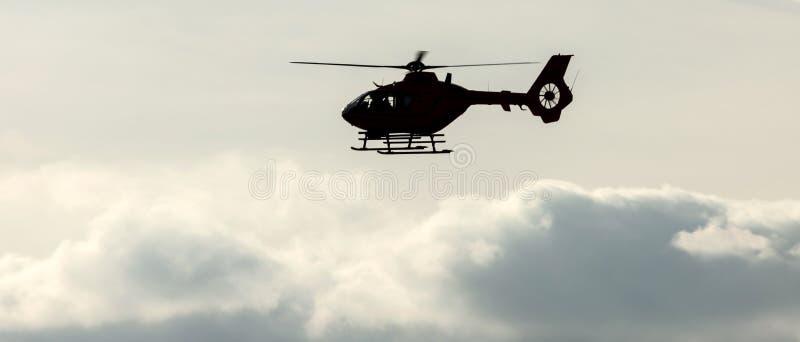在一平衡的cloudscape的直升机飞行 库存照片
