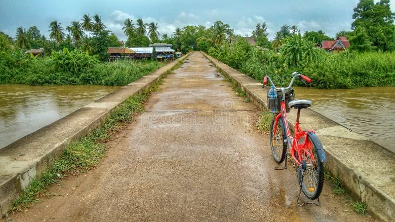 在一座具体桥梁的红色自行车在河湄公河在老挝的密林 免版税图库摄影