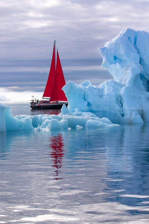 在一座巨型的冰山旁边的美丽的红色风船 库存图片
