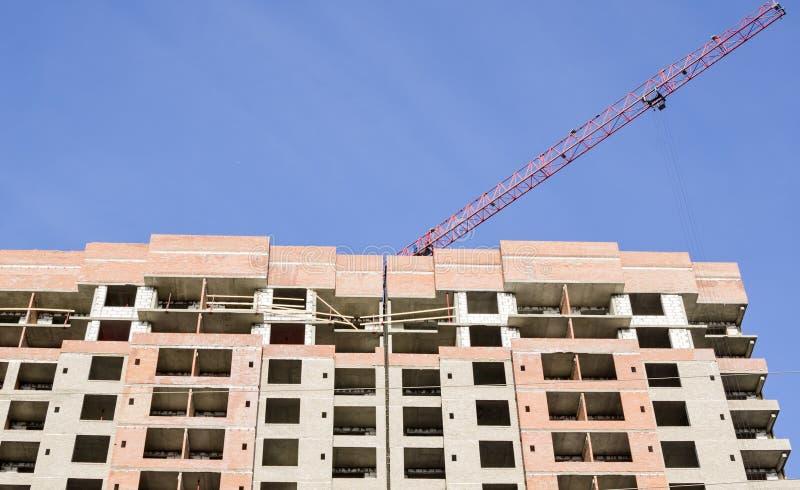 在一座高层建筑物的一个红色起重机箭头 免版税图库摄影