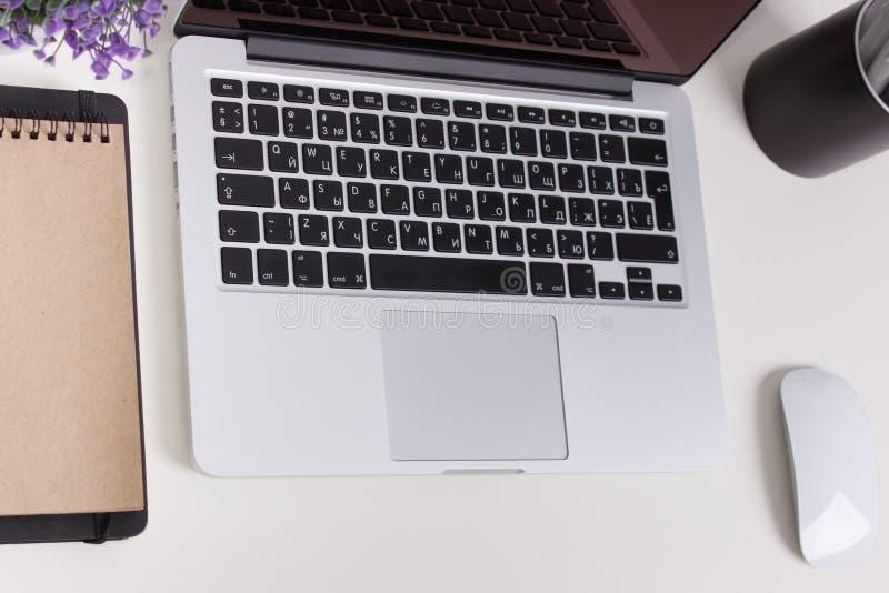 在一张书桌上的苹果计算机Macbook赞成视网膜有文具的 标签的,贴纸设计大模型 时髦办公室,自由职业者的工作场所 免版税库存图片