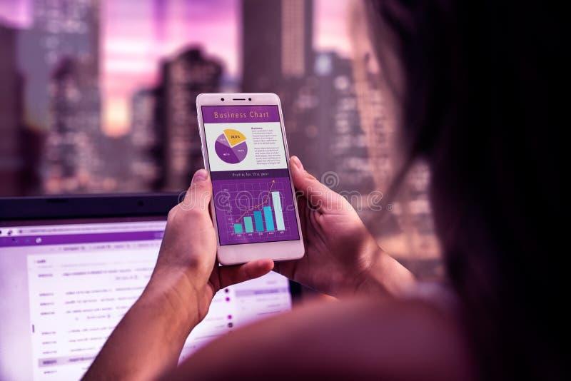 在一张书桌上的行政妇女有手机的在她的手上 在智能手机屏幕上的企业应用程序  工作在晚上 任命的 库存图片