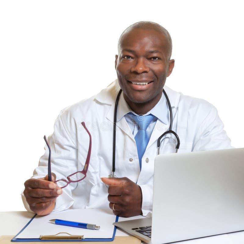 在一张书桌上的非洲医生有玻璃的在他的手上 库存图片