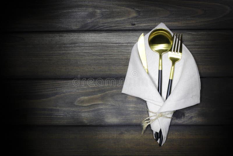 在一张亚麻布餐巾的利器在木黑暗的背景 匙子,叉子,在一个木板的刀子 厨房镀金了辅助部件, 库存图片
