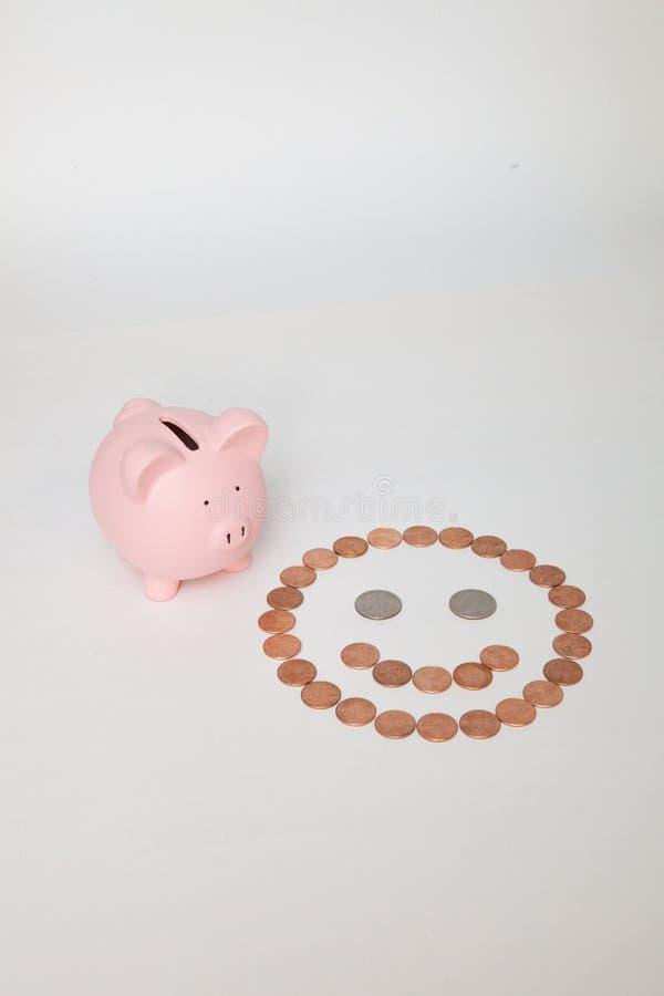 在一张兴高采烈的面孔旁边的存钱罐 免版税库存图片
