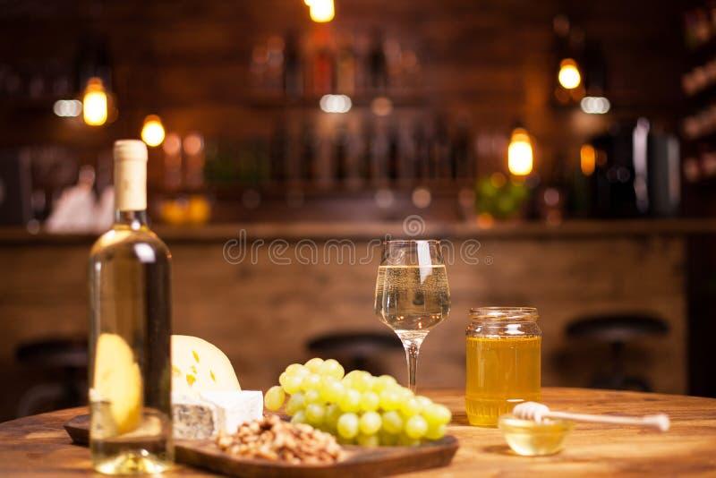 在一张土气书桌上的伟大的白酒在乳酪品尝事件在葡萄酒客栈 免版税库存照片