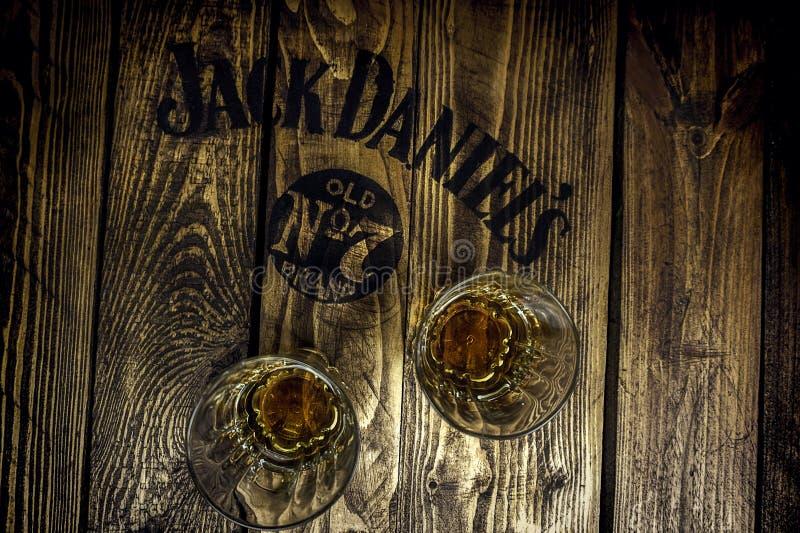 在一张土气木板台桌上的杰克丹尼尔的标志与威士忌酒玻璃 图库摄影
