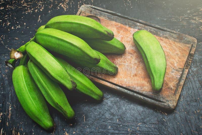 在一张土气木桌上的绿色香蕉 免版税库存照片