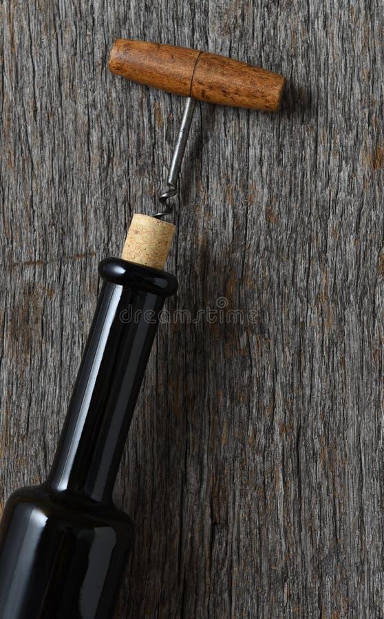 在一张土气木桌上的酒瓶与在黄柏插入的一个古色古香的拔塞螺旋拔出部分地  库存图片