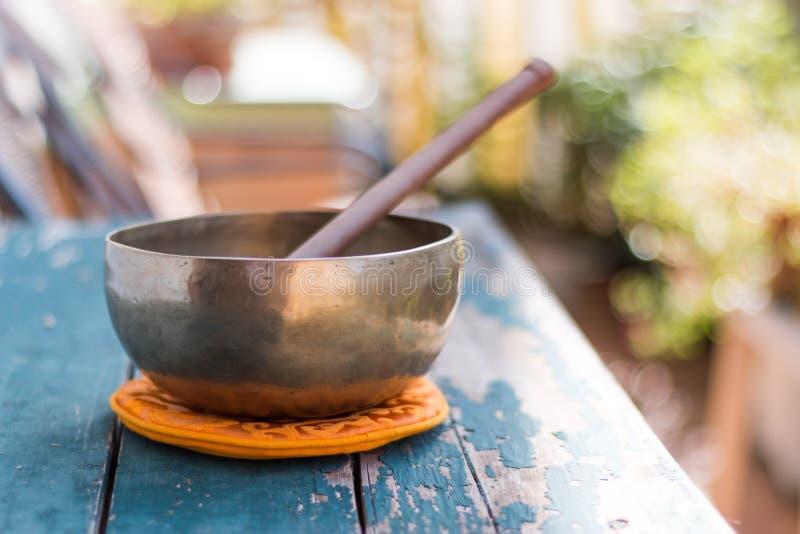 在一张土气木桌与花,禅宗上的唱歌碗,户外 免版税库存图片