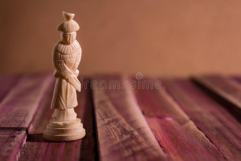 在一张土气桌上的孤零零棋子与带红色口气 库存图片