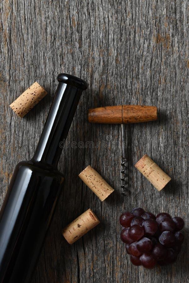 在一张土气老木桌上的酒瓶用葡萄、拔塞螺旋和黄柏 免版税库存照片
